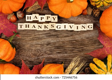 Happy Thanksgiving wooden blocks, above view with autumn frame over rustic wood