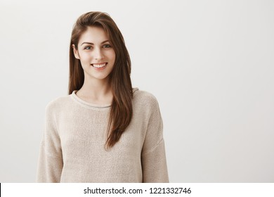 Happy that everything is okay. Portrait of charming friendly caucasian girl in casual sweater smiling cheerfully while standing against gray background, listening order or talking to coworker