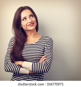 Happy thinking casual girl with folded hands looking up. Closeup vintage portrait with empty copy space