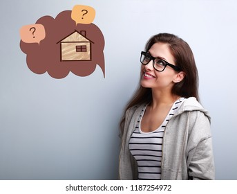 Happy thinking casual woman in eyeglasses looking up on illustration house in bubble cloud above with questions sign. Insurance protection concept, investment to safety money.