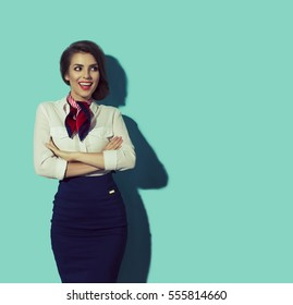 Happy thinking woman looking to the left. Young beautiful hostess with big smile on blue background.