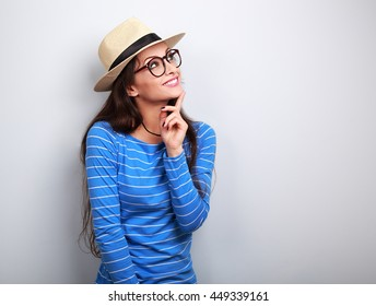 Happy thinking young woman looking up in fashion glasses and straw hat on blue background with empty copy space