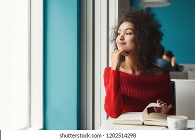 Happy thoughtful african-american girl at cafe table. Young woman enjoying hot coffee and reading favorite book, looking at window. Leisure, education and urban lifestyle concept.