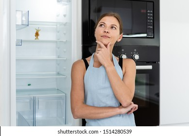 Happy and thoughtful young adult woman in apron looking away, standing on kitchen near opened refrigerator with apple stub at empty shelf