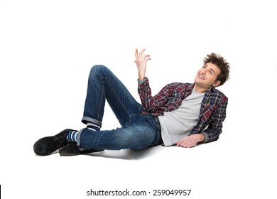 Happy thoughtful young man lying on the floor and looking up at copyspace