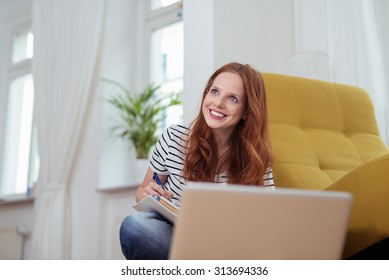 Happy Thoughtful Young Woman Thinking Something to Write While Sitting on the Floor at Home.