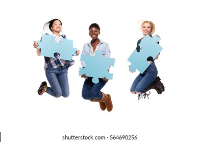 happy three different women, asian, caucasian and afro american, jumping with joy showing puzzle pices on white background
