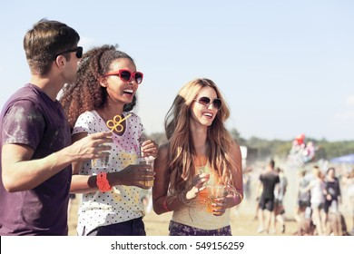 Happy three friends with drinks relaxing during summer festival in the fresh air