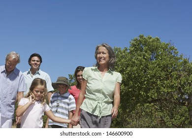Happy three generation family walking against clear blue sky