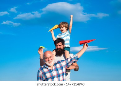 Happy three generations of men have fun and smiling on blue sky background. Father and son playing outdoors. Airplane ready to fly. Cute son with dad playing outdoor