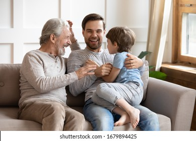 Happy three generations of men sit relax on couch in living room having fun together, overjoyed small preschooler boy play with young dad and elderly grandfather, enjoy family weekend at home