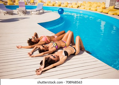 Happy three girls sun bathing near the pool. Attractive skinny girlfriends lie on white wooden floor on their backs, posing flirty in colorful swimming suits. They are so hot and tempting, elegant