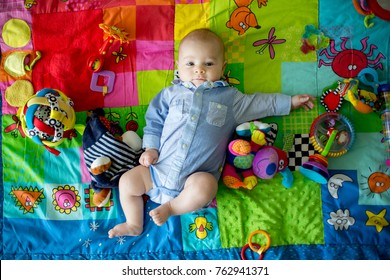 Happy three months old baby boy, playing at home on a colorful activity blanket, toys and different activity around him