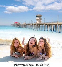 happy three teen friends girls lying on beach sand smiling at Huntington Beach California  [ photo-illustration]