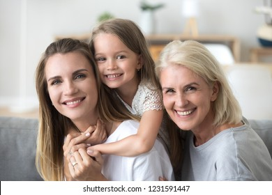 Happy three women generation, smiling young mother piggybacking little kid daughter looking at camera with old grandma, senior grandmother millennial mom and child together, family headshot portrait