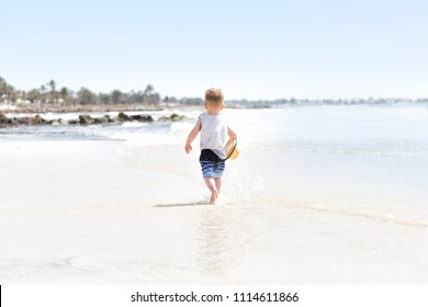 Happy three years old child boy in yellow hat running at white sand and jumping in the waves during summer vacation on tropical beach near blue sea. Smiling and cute toddler kid at the sea