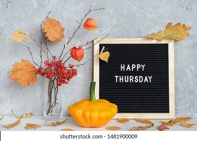 Happy Thursday text on black letter board and bouquet of branches with yellow leaves on clothespins in vase on table Template for postcard, greeting card Concept Hello autumn Thursday.