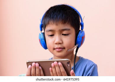 Happy time Asian's boy watching and listening to movie in mobile phone.Happy and relaxation time for a children.