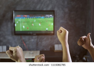Happy time of friendship watching football game on TV and celebrating victory at home.Friendship, sports and entertainment concept.