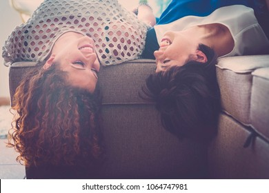 happy time with fun for a couple of young woman laughing and smiling at home lay down on the sofa. best firends forever with secrets concept.