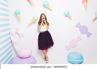Happy time of joyful young woman in tulle skirt isolated on white background among sweets. Pastel colors, macaroons, ice cream, happiness, fashionable model, having fun