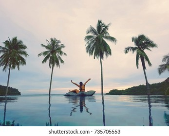 Happy time in private swimming pool in sea beach front side view with copy space for greeting cards. Silhouette view of coconut trees and asian girl with summer concept.