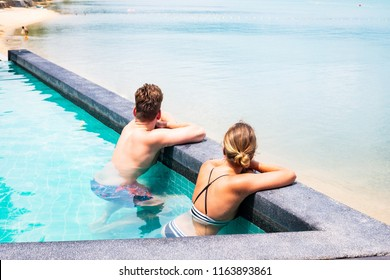 Happy  time and relaxation of couple with sun bath in a  pool swim,vacation concept