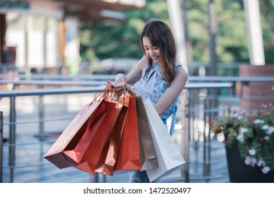 Happy time to shopping concept , Asian woman holding shopping bags at mall centre.