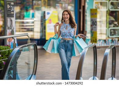 Happy time to shopping concept , Asian woman holding shopping bags at mall.