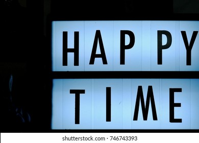 Happy time signboard with white light at the night and black background