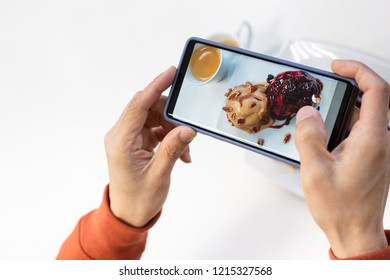 Happy time of young man using smart phone taking photo which take a picture food or bakery before eating, photography on white background