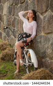 happy tired girl with bike resting near old stone wall