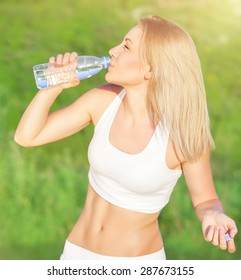 Happy tired woman drink water after workout in the park, enjoying training outdoors in sunny day, sportive and healthy lifestyle