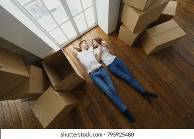 Happy but tired young couple lie on the floor of their new home. top view