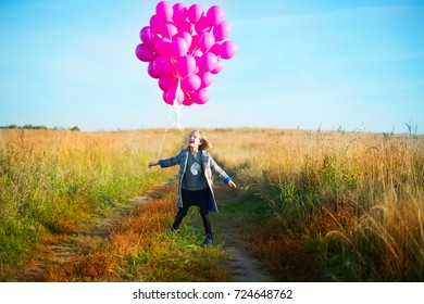 Happy toddler birthday girl in autumn field holding many pink balloons,dancing and laughing ready to celebrate holiday