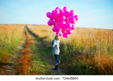 Happy toddler birthday girl in autumn field holding many pink balloons,smiling and laughing ready to celebrate holiday