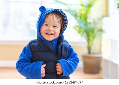 Happy toddler boy bundled up in winter clothes ready to go outside