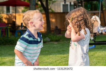 Happy Toddler Boy & Girl Laughing, Holding Hands and Playing in a Backyard Together