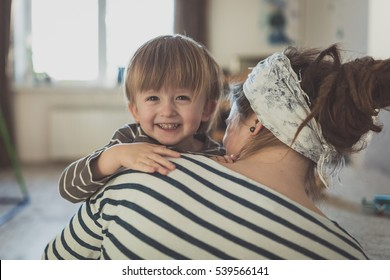Happy Toddler boy hugging his mother, close-up, feeling, the real interior, soft focus, light toning, concept and childhood dreams