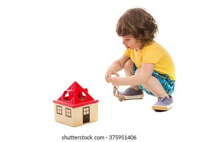 Happy toddler boy opening toy house isolated on white background
