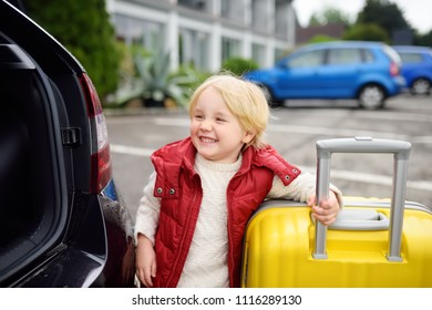 Happy toddler boy ready for going to road trip with his parents. Automobile trip in the countryside. Roadtrip for family with little kids