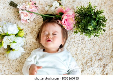 Happy toddler boy with spring flowers on a white carpet