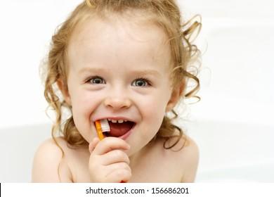 Happy toddler brushing teeth in the bath