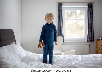 Happy toddler child, blond boy with blue pajama, jumping on the bed, holding little toy