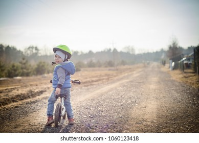 Happy toddler child boy riding on he's first bike without pedals. He's standing on road and looks back. Sport concept: kids ride bicycle; first bike; active toddler kid playing and cycling outdoors.