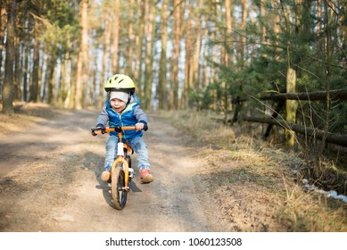 Happy toddler child boy riding bike without pedals. He rides off the hill with his legs raised. Sport concept: kids ride bicycle; first bike; active toddler kid playing and cycling outdoors.