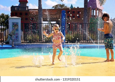 A happy toddler child is laughing as she jumps and plays in the water fountains at an outdoor spash park on a summer day.