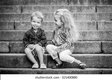 Happy toddler children sit on the steps outdoors  ( black and white )