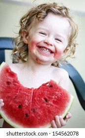 Happy toddler eating melon