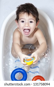 Happy toddler enjoying his bath moment. Making kid's bath-time fun / Happy Toddler taking a bath